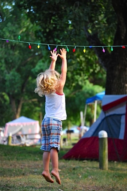 Little girl jumping up to touch a string of lights at a campground