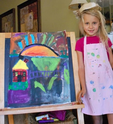 Little girl showing her art on an easel
