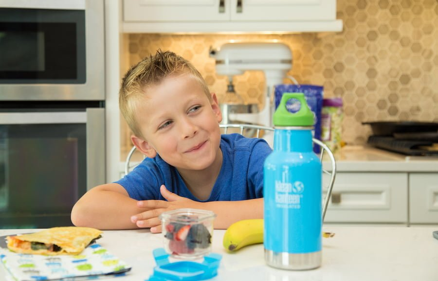 Elementary school boy with school lunch and reusable stainless steel water bottle