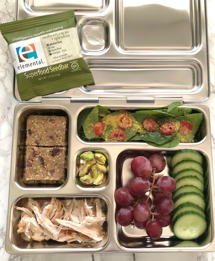 Healthy lunch ideas: Elevated Leftovers - Last night's grilled chicken, organic baby spinach with cherry tomatoes and nutritional yeast, sliced cucumbers, grapes, Elemental Superfood Seed Bar, and pistachios