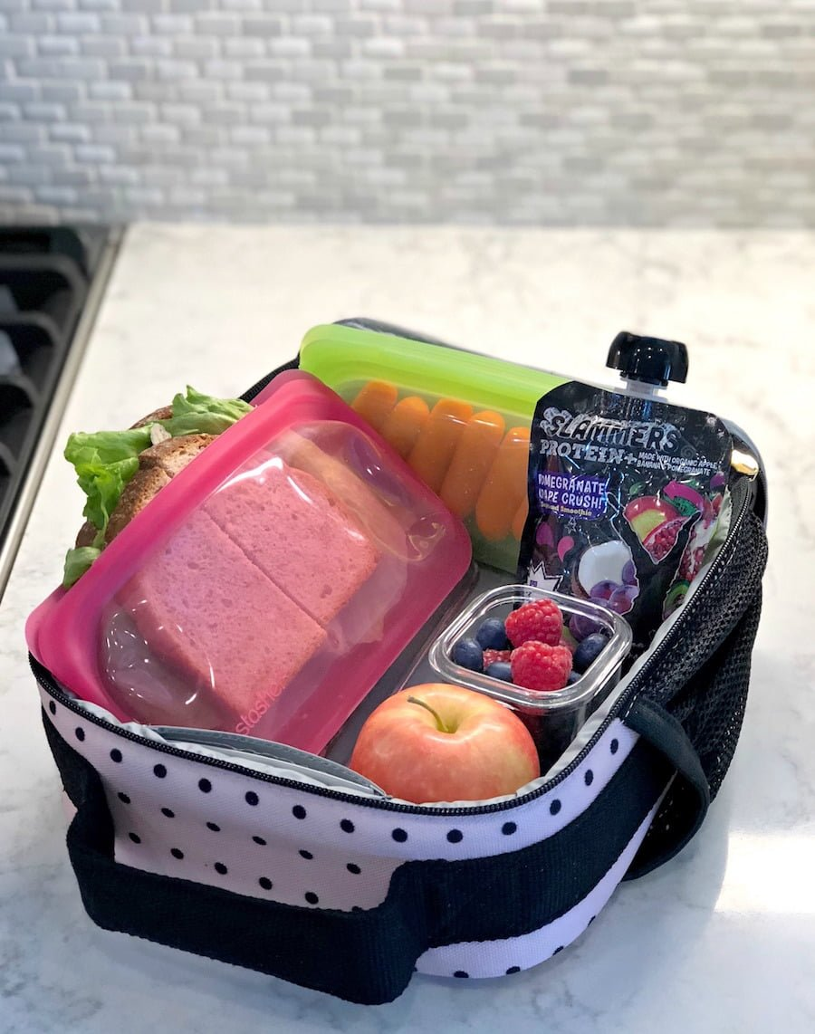 Healthy School Lunch Ideas Nitrate-free turkey sandwich, organic carrots, apple, blueberry and raspberry medley, and Pomegranate Grape Slammers Protein pouch in soft-sided lunch box