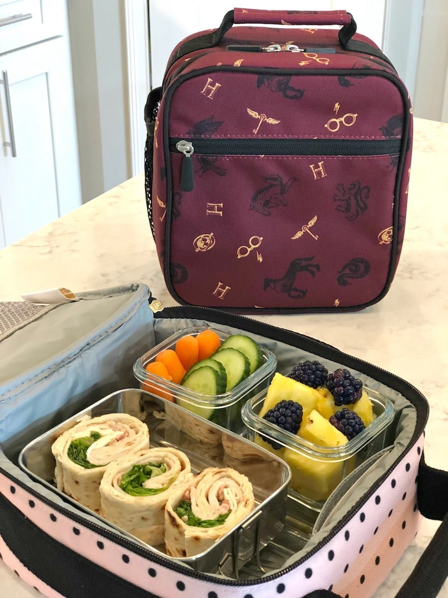 Healthy school lunch idea - Turkey, lettuce, cheese wraps with organic carrots, cucumbers, sliced pineapple, and blackberries.