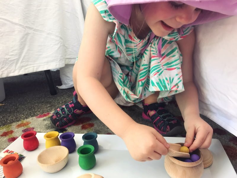 Child playing with age-appropriate wooden toys