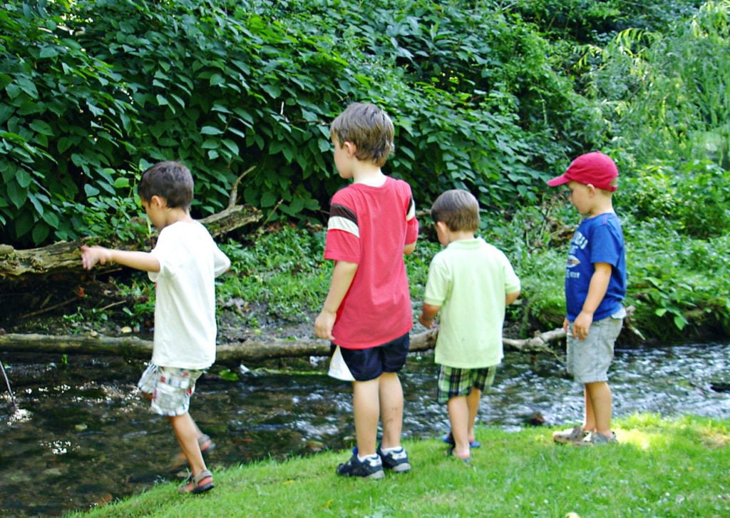 Kids playing near a stream Green Child Magazine photograph
