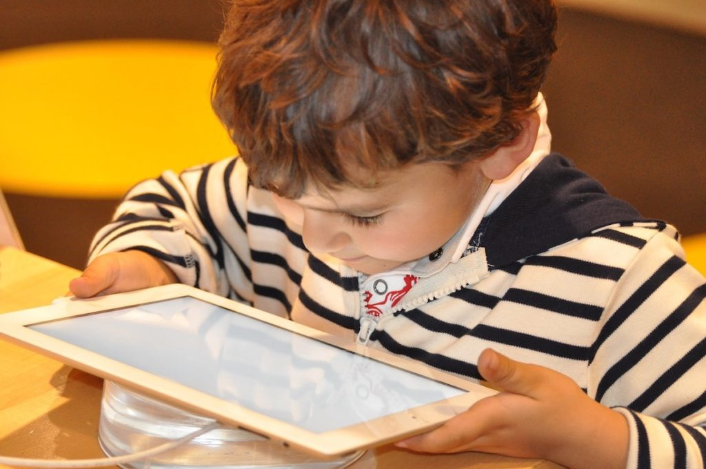 Child holding ipad up close, dangers of EMF exposure to kids