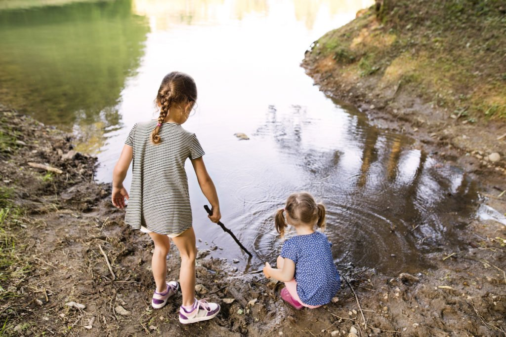 Young girls spending time in nature playing at the edge of a lake