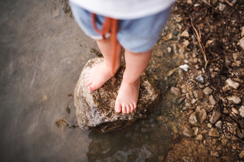 Child playing outside in nature with bare feet near the water