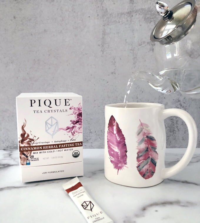 Pique Cinnamon Herbal Fasting Tea packets and mug of Pique tea crystals filled with tea kettle