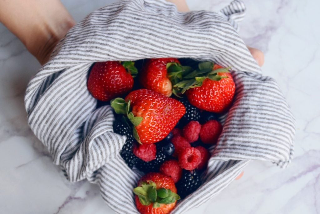Fresh summer berries in dish towel on white marble countertop