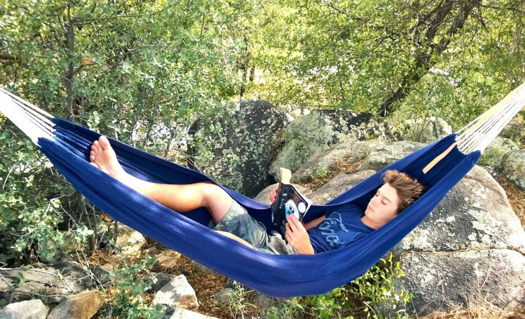 Homeschooled Boy reading in a hammock