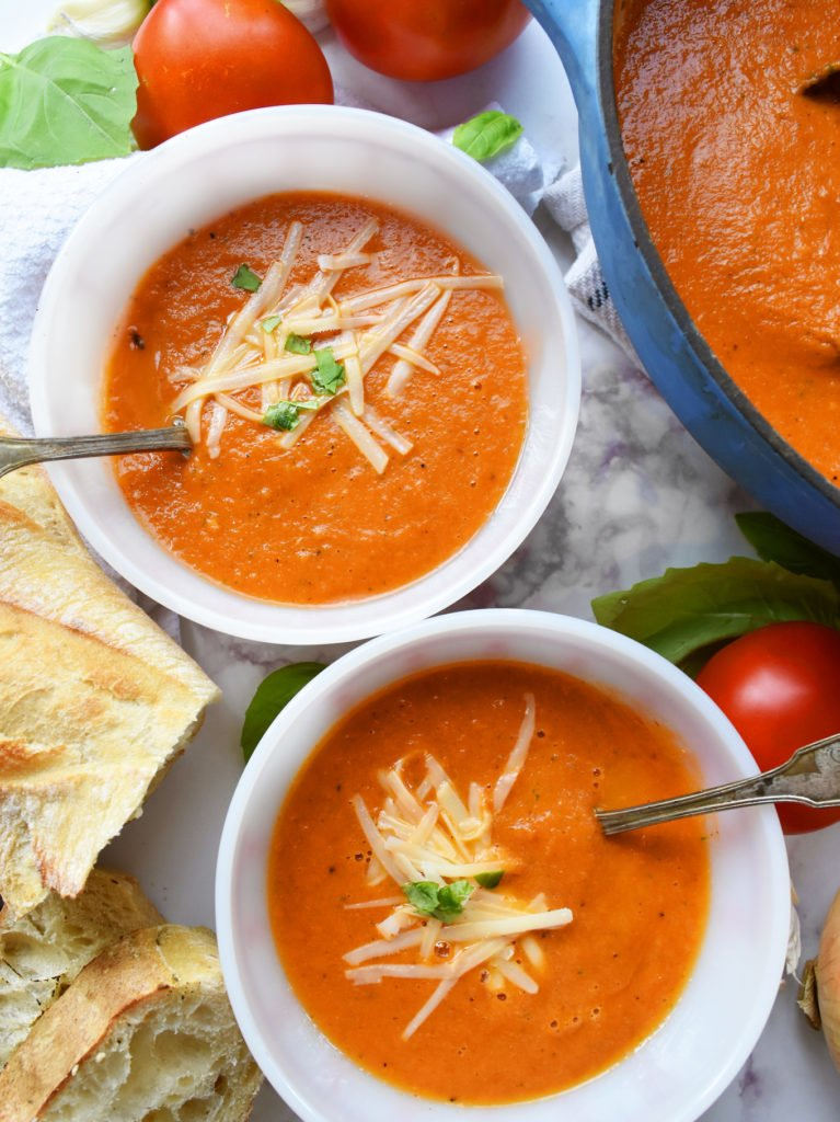 Roasted tomato basil soup in two bowls by dutch oven