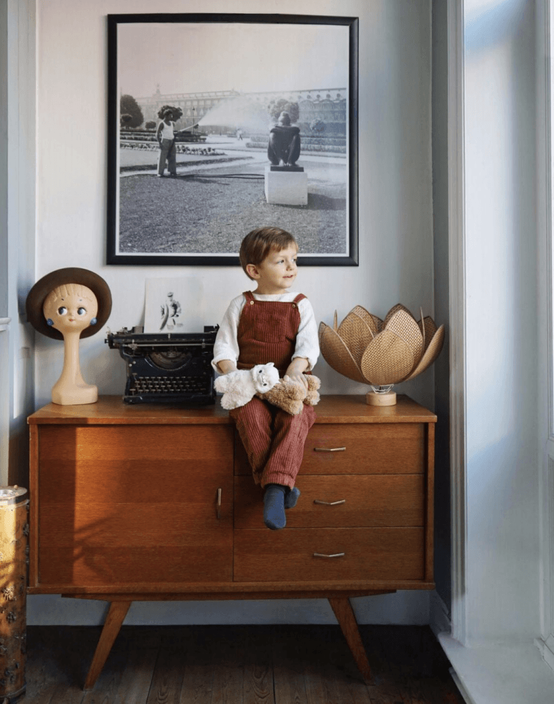 Child sitting on midcentury modern dresser looking out window
