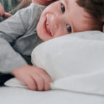 toddler boy in bed with mother